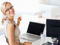 Portrait of smiling young business woman at office desk with laptop