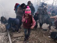 TOPSHOT - A child coughs as migrants and refugees run away after Macedonian police fired tear gas at hundreds of Iraqi and Syrian migrants who tried to break through the Greek border fence in Idomeni, on February 29, 2016. Greek police said more than 6,000 people were massed at the border, in a buildup triggered by Austria and Balkan states capping the numbers of migrants entering their territory. / AFP / LOUISA GOULIAMAKI