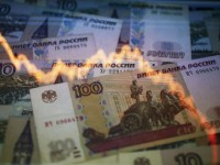 File photo illustration shows a reflection of a yearly chart of U.S. dollars and Russian roubles on rouble notes in Warsaw, Poland, November 7, 2014. The Russian rouble weakened to a new record low against the dollar on January 20, 2016, as the mood on global markets was torrid and oil prices slumped. REUTERS/Kacper Pempel/Files