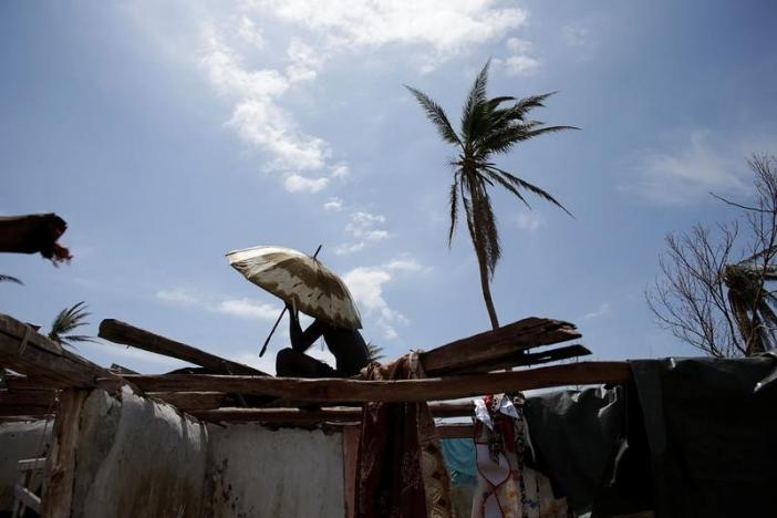 A man sits covering himself with an umbrella on the roof of a house affected by Hurricane Matthew in Port-a-Piment, Haiti, October 9, 2016. REUTERS/Andres Martinez Casares