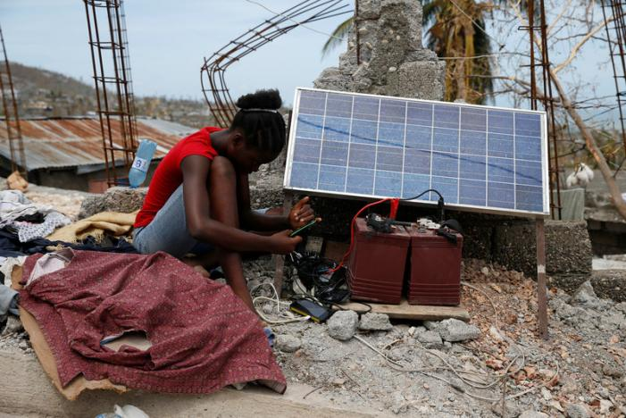 A woman looks at her mobile phone as it charges through solar panels after Hurricane Matthew passes in Jeremie, Haiti, October 9, 2016. REUTERS/Carlos Garcia Rawlins